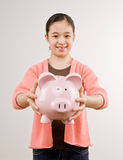 Girl holding piggy bank full of savings Stock Images