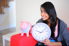 Girl holding piggybank and clock Royalty Free Stock Photos