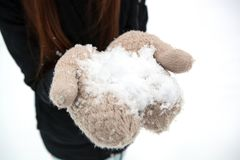 Girl holding a pile of snow in her hands Royalty Free Stock Images