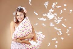 Girl holding pillow. Beautiful teenage girl holding a pillow studio shot Stock Photography