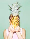 Girl holding pineapple. royalty free stock photos