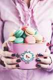 Girl holding pink bowl full of various macaroons Royalty Free Stock Photos