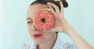 Girl holding pink donut looking through hole stock footage