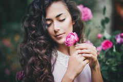 Girl holding a pink rose in her hands. Beautiful girl with long curly hair holding a pink rose in her hands in a rose garden Stock Images