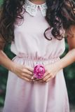 Girl holding a pink rose in her hands. In a park Stock Photos