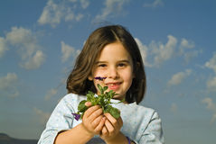 Girl holding plant. Girl with one tooth missing holding plant with flower Stock Photo