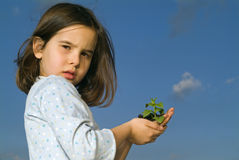 Girl holding plant. Against blue sky with a cloud Royalty Free Stock Image