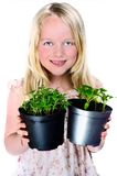 Girl Holding Plants. Smiling girl holding two pots of plants, tomato and chilli seedlings, isolated on white Royalty Free Stock Photography