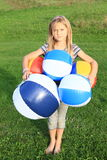 Girl holding planty of inflating balls Stock Photos