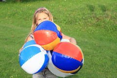 Girl holding planty of inflating balls Royalty Free Stock Images
