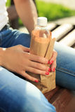 Girl holding a plastic bottle in a paper bag Royalty Free Stock Photo