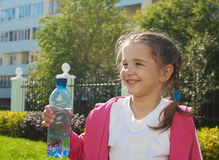 Girl holding a plastic bottle with water. On sunny summer day Royalty Free Stock Photos