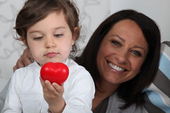 Girl holding plastic heart Royalty Free Stock Photography