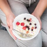The girl is holding a plate of cottage cheese. Healthy eating concept. Cottage cheese with berries. Girl in home clothes. Proper nutrition. Diet. Plump girl Stock Images