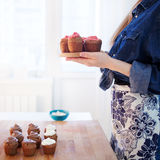 Girl holding plate of fresh hot muffins, blurred Royalty Free Stock Image