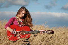 Girl holding playing guitar in field. Young longer-haired fashined woman holding a guitar in field against blue cloudy sky and field background. Autumn Royalty Free Stock Photography