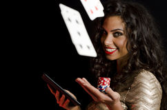 Girl holding poker chips and tablet, black background Royalty Free Stock Image