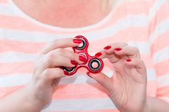 A girl is holding a popular toy fidget spinner in her hands. Stress relief. Anti stress and relaxation fidgets, spinner for tired. People. Girl playing with a royalty free stock photos