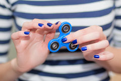 A girl is holding a popular toy fidget spinner in her hands. Stress relief. Anti stress and relaxation fidgets, spinner for tired. People. Girl playing with a royalty free stock photography