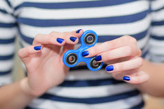 A girl is holding a popular toy fidget spinner in her hands. Stress relief. Anti stress and relaxation fidgets, spinner for tired Stock Images