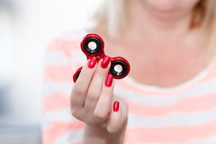 A girl is holding a popular toy metallic red fidget spinner. A girl is holding a popular toy metallic red fidget spinner in her hands. Stress relief. Anti stock photos