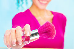 Girl holding powder brush, focus on brush Stock Photo