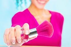 Girl holding powder brush, focus on brush. Smiled girl holding powder brush, focus on brush Stock Photo