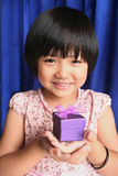 Girl holding present. Little girl smiling and holidng purple gift box Royalty Free Stock Photography