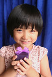 Girl holding present. Little girl smiling and holidng purple gift box Stock Photography