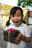 Girl holding present. Happy girl surprising and holding a black gift box with ribbon Stock Photo
