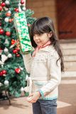 Girl Holding Present In Courtyard Stock Photo