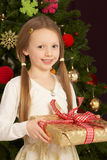 Girl Holding Present In Front Of Christmas Tree Stock Photos