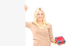 Girl holding a present next to a blank panel Royalty Free Stock Image