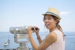 Girl holding public binoculars at the seaside wearing pink dress Royalty Free Stock Images