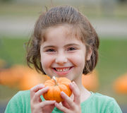 Girl Holding a Pumpkin Royalty Free Stock Images