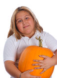 Girl Holding Pumpkin. A young girl holding a heavy and large pumpkin, isolated against a white background Stock Images