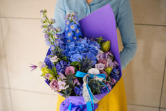 Girl holding purple and pink flower bouquet. No face Stock Photos