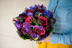 Girl holding purple and pink flower bouquet. No face Royalty Free Stock Photography