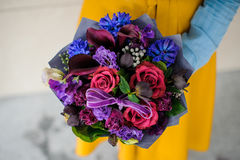 Girl holding purple and pink flower bouquet. No face Stock Images