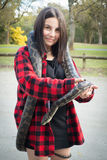 Girl holding python snake. Young teenager holding a python snake outdoors Stock Photo