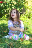 Girl holding rabbit. Smiling young girl holds a rabbit in her lap Royalty Free Stock Image