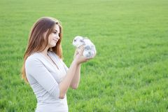 Girl holding a rabbit while on a green meadow. royalty free stock photos