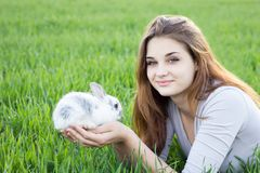 Girl holding a rabbit while on a green meadow. stock photo