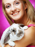 Girl holding rabbit on hand Stock Image