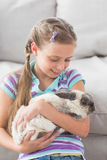 Girl holding rabbit in living room Royalty Free Stock Images
