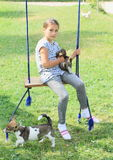 Girl holding rabbit on swing Stock Images
