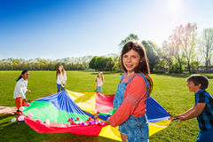 Girl holding rainbow parachute with colorful balls. Portrait of young girl standing in a circle with her friends and holding rainbow parachute full of colorful stock image