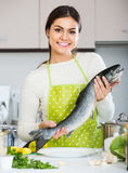 Girl holding rainbow trout in domestic kitchen. Pretty european girl holding rainbow trout in domestic kitchen royalty free stock photos