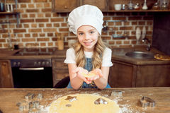 Girl holding raw heart shaped dough for cookie Stock Photo