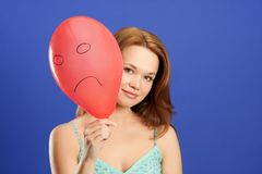 Girl holding red angry balloon Royalty Free Stock Photography